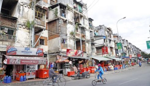 People cycle past Phnom Penh's White Building yesterday afternoon. Local authorities have warned residence of the building that overloaded apartments could lead to future dangers. Pha Lina