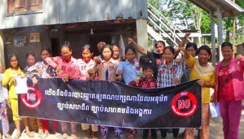 Community members hold a banner during a protest against the controversial NGO law yesterday in Svay Rieng province. ADHOC