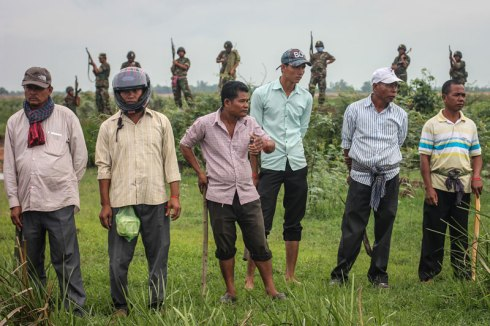A row of Cambodian men armed with wooden clubs stand in front of Cambodian soldiers about a kilometer from the Vietnamese border in Svay Rieng province, where they confronted hundreds of activists who were led to the area by a group of opposition lawmakers Sunday. (Alex Willemyns/The Cambodia Daily)