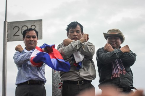 From left: CNRP lawmakers Un Sam An, Real Camerin and Cheam Channy pose while standing on border post 203 on Sunday. (Alex Willemyns/The Cambodia Daily)