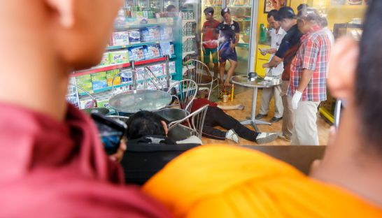 monks_peer_through_the_window_of_a_caltex_star_shop_as_investigators_inspect_the_body_of_kem_leyafter_he_was_shot_on_sunday_morning_10_07_2016_pha_lina