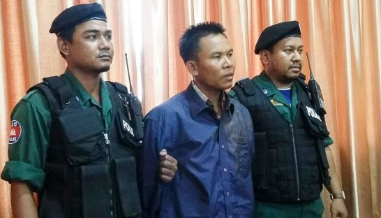 police_stand_next_to_oeut_ang_earlier_this_month_at_the_phnom_penh_municipal_police_headquarters_after_he_was_arrested_for_the_murder_of_political_analyst_kem_ley_16_07_2016_supplied