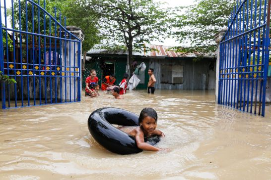 a_child_plays_in_flood_waters_with_an_inner_tube_yesterday_at_phnom_penhs_spean_thma_commune_17_10_2016_pha_lina