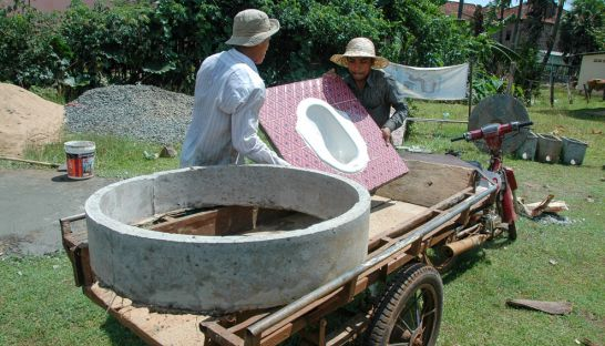 people_unload_building_materials_from_a_trailer_in_kampong_cham_during_the_construction_of_a_latrine_in_2012_as_part_of_a_campaign_to_eliminate_open_defecation_plan_international