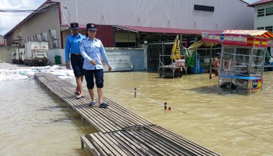 security_guards_walk_over_a_makeshift_footpath_on_phnom_penhs_chamka_doung_road_yesterday_after_flood_waters_inundated_the_area_19_10_2016_jey_chue_xue_ting