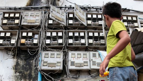 a_young_boy_walks_past_power_meters_at_the_white_building_in_phnom_penh_earlier_this_year_hong_menea