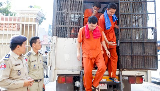 mao_hoeung_right_and_chhay_sarith_center_exit_a_prisoner_transport_vehicle_earlier_this_year_at_the_phnom_penh_municipal_court_ahead_of_a_hearing_10_05_2016_pha_lina