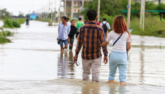 people_make_their_way_along_a_flooded_street_on_the_outskirts_of_phnom_penh_last_month_after_heavy_rain_caused_flooding_heng_chivoan