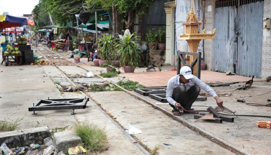 3_a_man_in_phnom_penh_yesterday_works_beside_an_unused_railway_track_which_will_be_developed_into_a_new_road