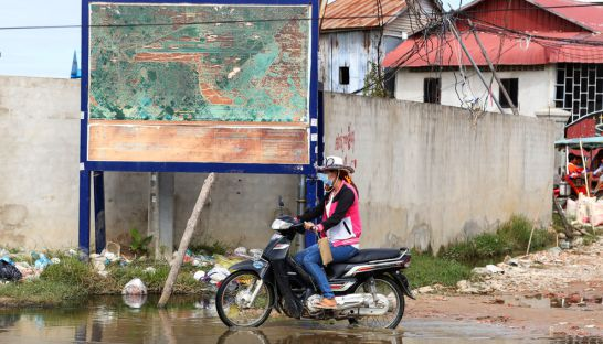 3_a_woman_yesterday_rides_past_a_billboard_displaying_a_map_of_the_proposed_extension_of_phnom_penh_international_airport_in_the_citys_thmor_kol_commune_19_12_2016_heng_chivoan