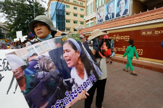 Protesters carry posters of Boeung Kak activist Tep Vanny before her trial outside court yesterday. Heng Chivoan