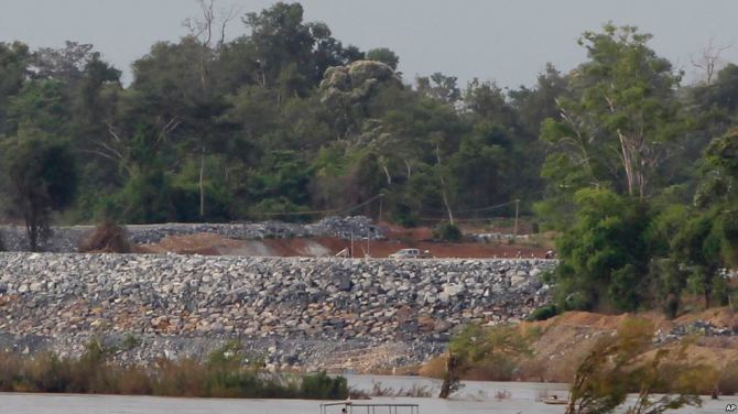 In this June 20, 2016, photo, a fishing boat drive near an under construction site of the Don Sahong dam on the Mekong river near Cambodia-Laos borders, in Preah Romkel village, Stung Treng province, northeast side of Phnom Penh, Cambodia. Landlocked Laos is the poorest state in Southeast Asia but by virtue of geography and growing Chinese influence, its secretive authoritarian leaders wield a huge and unaccountable power over a river that winds through six. (AP Photo/Heng Sinith)