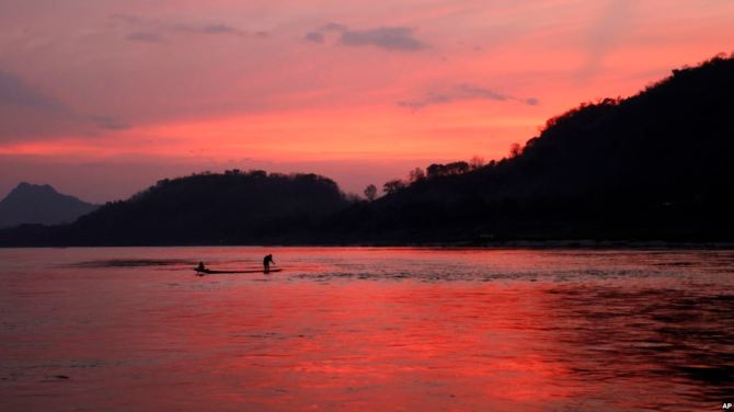In this March 4, 2011, file photo, men ride in a boat across the Mekong River in Luang Prabang, Laos. It is officially described as the best-preserved city in Southeast Asia, a bygone seat of kings tucked into a remote river valley of Laos. Luang Prabang weaves a never-never land spell on many a visitor with its tapestry of French colonial villas and Buddhist temples draped in a languid atmosphere. (AP Photo/Jacquelyn Martin, File)