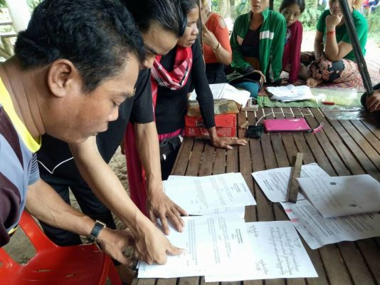 Villagers in Kandal province sign a complaint against local businesswoman Eat Sarim, who they say cheated them out of hundreds of dollars each by promising them jobs in Japan. Supplied